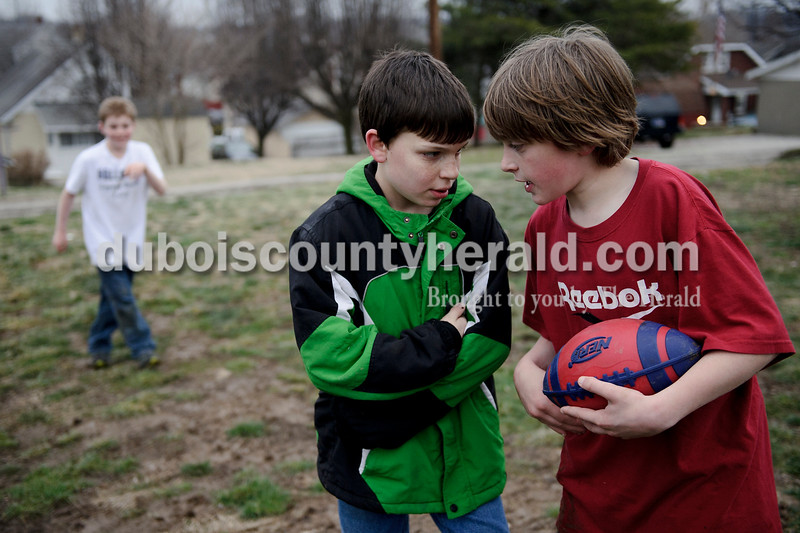 Matthew Busch/The Herald<br /> Quentin Lechner, 11, second right, listened to Andrew Franklin, 10, right, as they planned out a pass play against Dayton Shelton, 11, left, during a game of football outside Franklin's home after school on Tuesday. The three friends are from Jasper and all attend 10th street elementary.