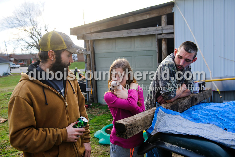 Matthew Busch/The Herald<br /> Hannah Rasche of Dubois, 9, second right, kissed Rider the dog as her father Robert Rasche of Dubois, left, and Cody Cooper of Dubois, right, talked with family and friends outside of Rasche's home on Friday afternoon in Dubois.