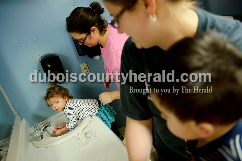 Matthew Busch/The Herald<br /> Tempe Curtsinger, 1, left, washed her hands before snack time with the help of her teacher Jenny Polley at HUMmingbird Day Care in Holland on Tuesday. The teachers at HUMmingbird have begun taking extra preventative measures for protecting their students and themselves against the recent outbreak of the flu virus. Teacher Krystal Sutt, second right, helped Rylan Christison, 2, wash his hands as well.
