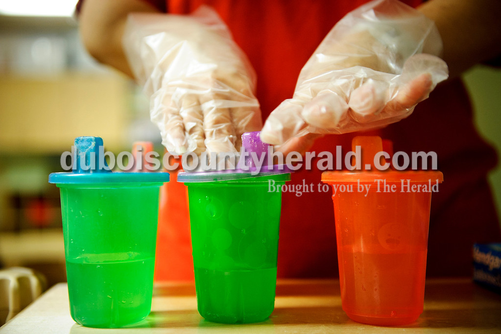 Matthew Busch/The Herald<br /> Darlene Jacobson, a teacher at HUMmingbird Day Care in Holland, wore plastic gloves as she added the lids to her toddler students' sippy cups on Tuesday. The Teachers at HUMmingbird always wear these gloves when handling food for their students.