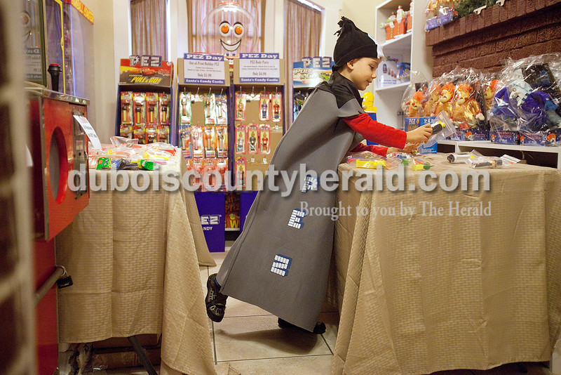 Rachel Mummey/The Herald<br /> Dean Knight of Cannelton, 8, inspected PEZ dispensers while sporting a homemade PEZ costume made by his mother, Amy, at Santa's Candy Castle in Santa Claus during their PEZ day celebration Saturday. Dean, who is an avid collector of PEZ dispensers, saved all his money throughout the entire year just so he was prepared for the event. He had a total $40 to spend.