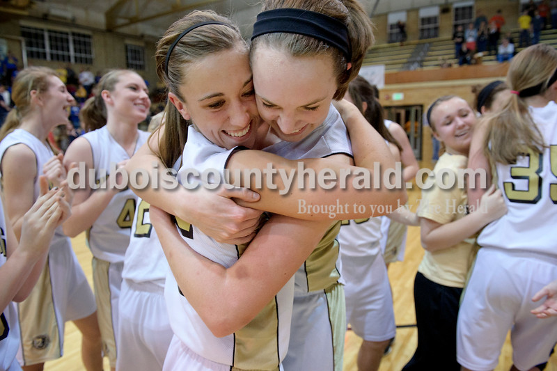 Matthew Busch/The Herald<br /> Jasper's Allyson Lents, left center, and Shelby Merder, right center, hugged after defeating Mitchell during Saturday's Class 3A girls sectional at Cabby O'Neil Gymnasium in Jasper. The WIldcats won 66-53.