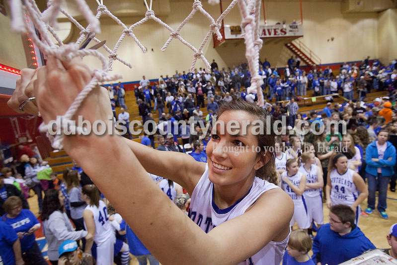 Rachel Mummey/The Herald<br /> Northeast Dubois' Rachel Breitwieser clipped a section of the game net after winning the Class 1A girls sectional championship against Tecumseh in Lynnville on Saturday. Northeast Dubois won 49-42.
