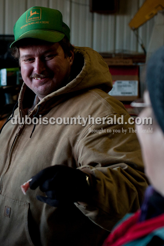 Matthew Busch/The Herald<br /> Keith Humbert of Dubois, left, teased his girlfriend of 13 years, Renee Voelkel, with a piece of cut meat as the Humbert family and friends gathered to butcher hogs on Saturday in Dubois. The family has been butchering hogs in the area for over 50 years.