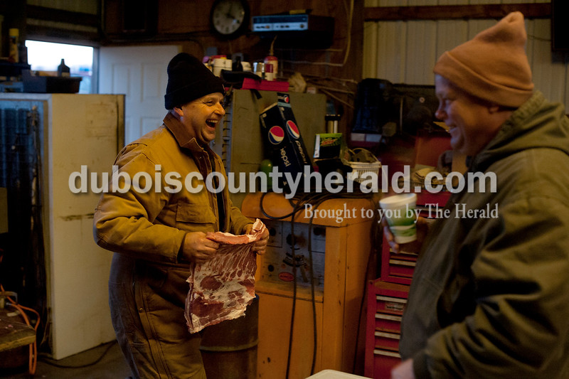 Matthew Busch/The Herald<br /> Mark Humbert, left, laughed as he carried a piece of hog meat to a back table as the four brothers of the Humbert family and their friends gathered to butcher hogs on Saturday in Humbert's shed in Dubois. The family has been butchering hogs in the area for over 50 years. Pat Zehr of Dubois, the four Humbert brothers' first cousin, is pictured right.