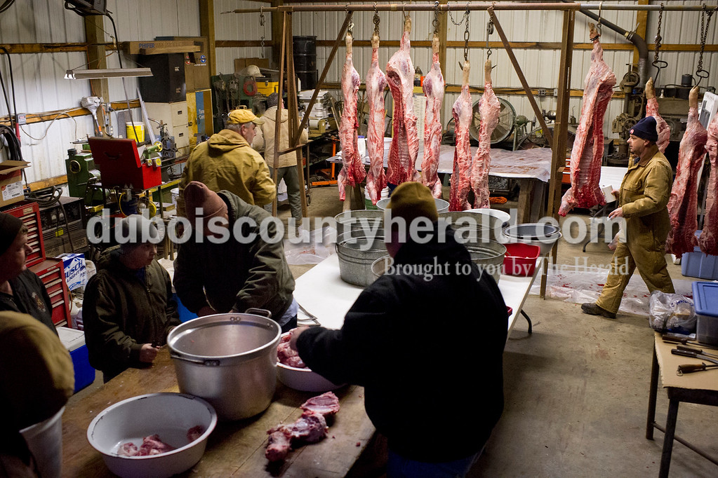 Matthew Busch/The Herald<br /> The Humbert family and friends gathered to butcher hogs on Saturday in Mark Humbert's shed in Dubois. The family has been butchering hogs in the area for over 50 years.