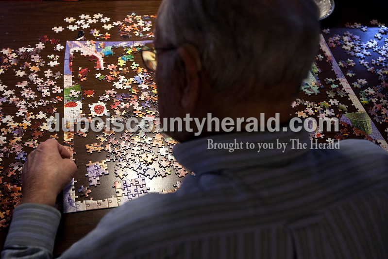 "Dave Weatherwax/The Herald<br /> Reynold ""Lenny"" Knust of Ferdinand worked on a 1,000-piece puzzle titled ""I Love Ice Cream!"" in the basement of his home Monday morning. The puzzle is a picture of an assortment of ice cream treats of varying colors."