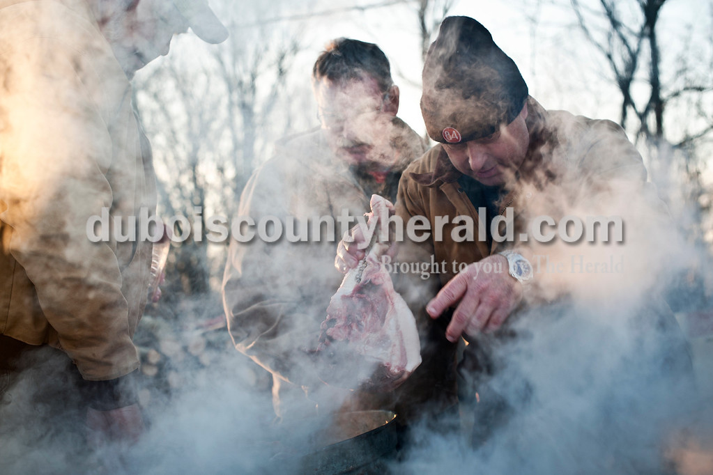 """Matthew Busch/The Herald<br /> Mark Humbert, right, pointed to where he needed to place the next piece of head meat into a boiling kettle as family friends, brothers Curt and Nick """"Cooter"""" Hall, handed him pieces of meat on Saturday during the Humbert family hog butchering. The Humbert family and friends gathered to butcher hogs on Friday and Saturday in Mark Humbert's shed in Dubois. The family has been butchering hogs in the area for over 50 years."""