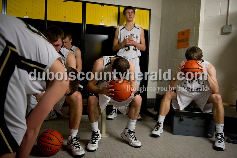 Jasper's Nate Messier, center, and Devon Traylor, right, rested their heads on basketballs in the locker room as they waited for the start of Tuesday's Class 3A boys sectional against Heritage Hills at The Hatchet House gymnasium in Washington. The Wildcats won 81-69 in overtime. Matthew Busch/The Herald