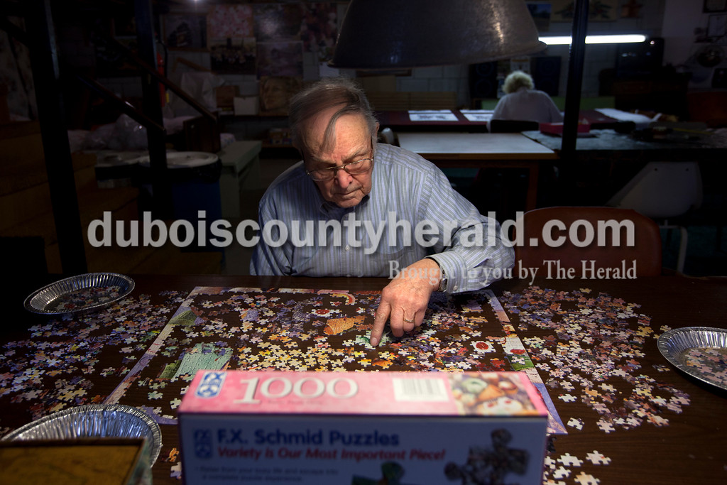 """Dave Weatherwax/The Herald<br /> """"You try a lot and a lot of pieces until you find the right one,"""" said Reynold """"Lenny"""" Knust, 86, as he worked on a 1,000-piece puzzle in the basement of his Ferdinand home Monday morning. When the former dairy farmer and his wife of 62 years, Leona, 82, moved from the farm into a house in town in 1994, Lenny picked up the hobby of working on puzzles. He has counted, but estimates that he's completed over 50 puzzles since. Leona is often working in the basement with him on her quilts."""