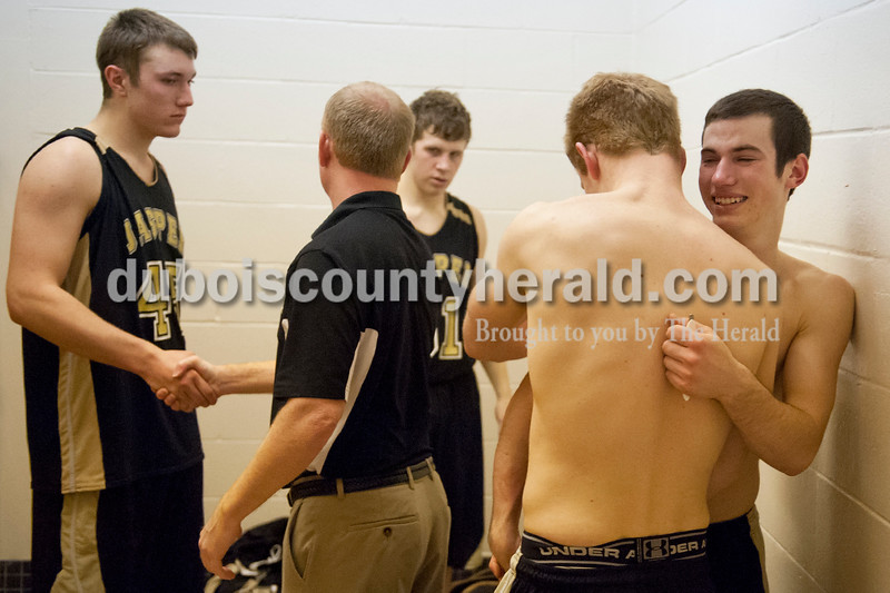 Jasper's Nate Messier, right, and Cole Sermersheim, second right,  hugged in the locker room after their loss to Vincennes Lincoln during Saturday's Class 3A boys sectional championship at the Hatchet House in Washington. The Wildcats lost 48-25. Matthew Busch/The Herald