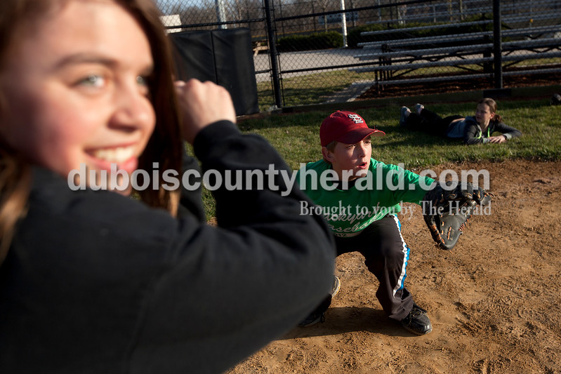 Dave Weatherwax/The Herald<br /> Kalen Jochum of Ireland, 10, left, stepped up to the plate as a batter, but without a bat, as Gavin Hopf of Jasper, 11, braced to receive the pitch while the two took turns with four other friends practiced throwing pitches on the secondary softball field at Jasper High School on Tuesday afternoon. The kids were passing time while the junior varsity softball game was taking place a field over between Heritage Hills and Jasper. Coverage of the varsity game between the Wildcats and Patriots is on Page 20 and at DuboisCountyHerald.com.
