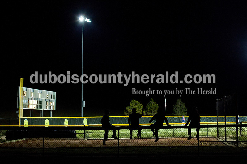 Noah Mundy of Santa Claus, 11, left, Carson Leibering of Santa Claus, 12, Sam Scott of Fulda, 11, and Taner Bauer of Dale, 11, sat atop the fence of a neighboring field while watching the Heritage Hills and Jasper varsity softball game in Jasper on Tuesday night. Dave Weatherwax/The Herald