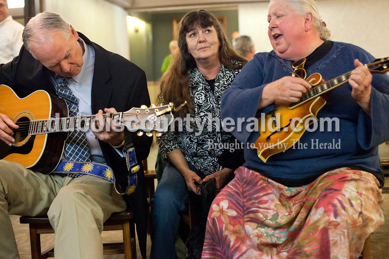 Dave Weatherwax/The Herald<br /> Clyde Melton of Celestine, left, Melinda Sketo of Paoli and Maria Abel-Crecelius of Paoli joined a handful of musicians during a jam session for the late Paul Michael Ash on Monday afternoon during Ash's visitation at Becher Funeral Home in Ferdinand. Ash died Thursday of prostate cancer caused by exposure to Agent Orange in the Vietnam War. Friends were encouraged to bring their instruments to participate in a music jam during the visitation for Ash, who was a self-taught singer-songrwiter who was known in the area for his music.