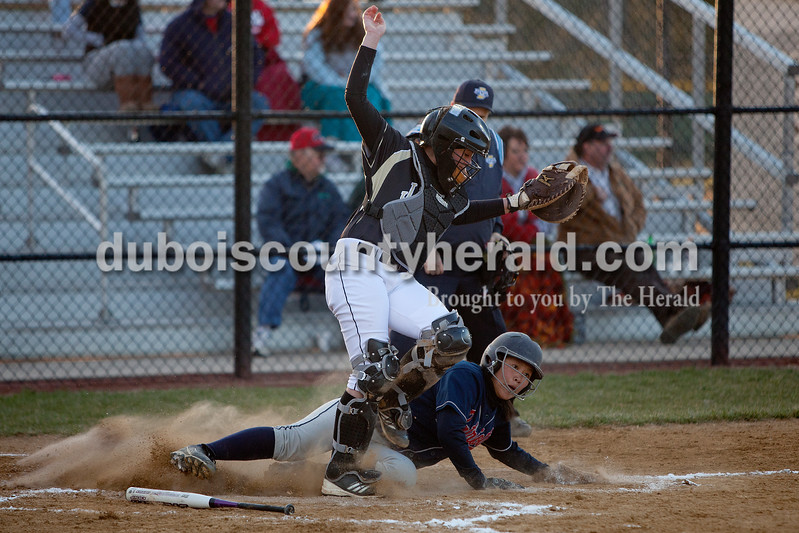 Heritage Hills' Hayli Scott slid safely into home plate under Jasper catcher Jessie Gudorf for the Patriots only run scored during Tuesday night's game in Jasper. The Wildcats defeated the Patriots 4-1.Dave Weatherwax/The Herald