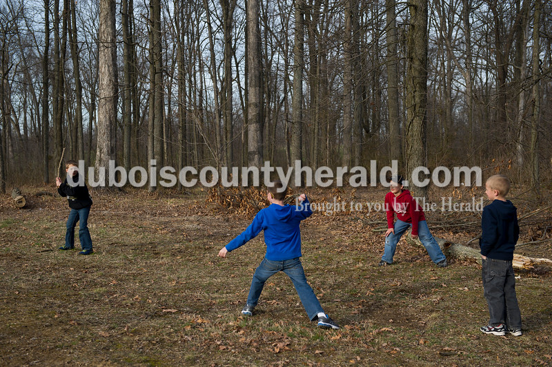Luke Nonte, 9, a third grader at Loogootee Elementary, left, Camren Giesler, 8, a third grader at Ferdinand Elementary, Wade Graber, 8, a third grader at Loogootee Elementary and Giesler's brother Carter Giesler, 6, a first grader at Ferdinand Elementary, played baseball using a stick for a bat, a rock for a baseball and a log for third base outside the ballpark during Heritage Hills' game against Loogootee Wednesday night in Lincoln City. Matthew Busch/The Herald