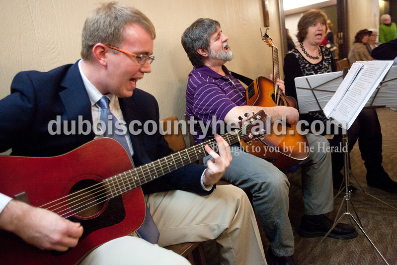 """Dave Weatherwax/The Herald<br /> Mike Cummings of Ferdinand, left, Mel Schroeder of Ferdinand and Joan Melton of Celestine sang The Beatle's """"Don't let me down"""" together with a handful of musicians during a jam session for the late Paul Michael Ash during his visitation Monday afternoon at the Becher Funeral Home in Ferdinand."""