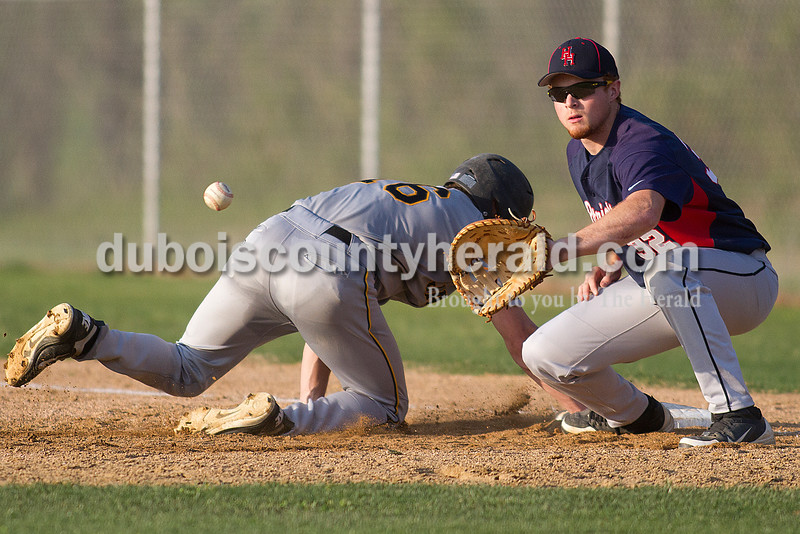 Rachel Mummey/The Herald<br /> Heritage Hills' first basement Miles Kline tried getting a tag out on Jasper's Nick Gobert during Monday night's game in Lincoln City. Jasper won 9-0.