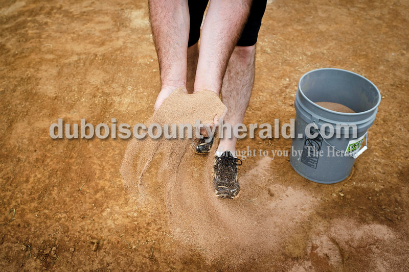 Jasper assistant coach Phil Kendall spreads extra dirt on the field to dry it out before the start of Jasper's game Tuesday against Princeton at Ruxer Field. The Wildcats won 4-2. Matthew Busch/The Herald