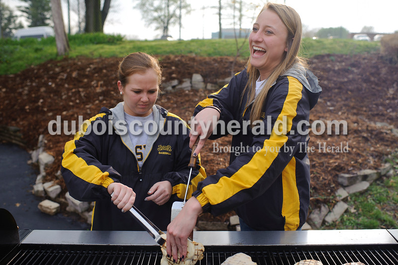 Jasper seniors Mikaela Lechner, right, and Caitlynn Wesseh, left, tried to unstick two frozen chicken patties from each other as they cooked up food for the concession stand during Jasper's game Tuesday against Princeton at Ruxer Field. The Wildcats won 4-2. Matthew Busch/The Herald