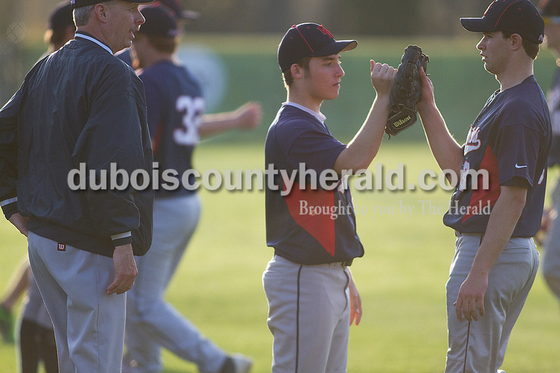 Rachel Mummey/The Herald<br /> Heritage Hills' Drew Grass fist bumped teammate Derrick Kippenbrock while getting words of encouragement from head coach Dave Sensenbrenner during Monday night's game against Jasper in Lincoln City. Jasper won 9-0.
