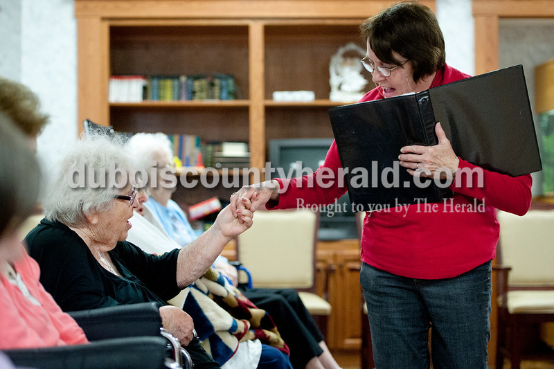 Matthew Busch/The Herald<br /> Singing senior Viola Heitz held hands and sang with Northwood Community Resident Judy Guthrie as the Singing Seniors from Dubois County sang songs for the residents in Jasper.