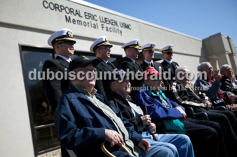 Army veteran Louie Lueken, bottom left, posed for pictures with fellow World War II veterans from the St. Charles Health Campus in Jasper and commanders of the Crane Division, Naval Support Activity in front of the natural resources building at Crane on Monday morning. The building was renamed the Corporal Eric Lueken, USMC Memorial Facility in honor of Louie's grandson on the seventh anniversary of the Marine's death. Eric was a 2001 Northeast Dubois High School graduate and died in action April 22, 2006, in Iraq. Dave Weatherwax/The Herald
