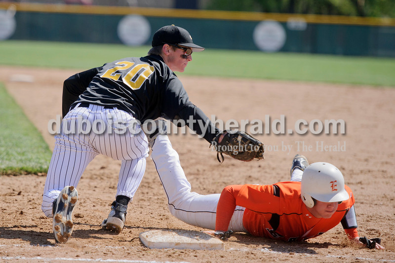Jasper's Spencer Otto tried to tag out a Columbus East player as he slid into first during Jasper's game Saturday against Columbus East at Ruxer Field. Matthew Busch/The Herald