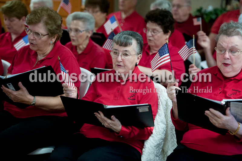 Matthew Busch/The Herald<br /> Singing seniors La Verne Reinbold of Huntingburg, left, Mikki Stemle of Jasper, and Pat Dunkel of Jasper, held American flags as the group from Dubois County sang songs for the residents at the Northwood Retirement Community in Jasper.