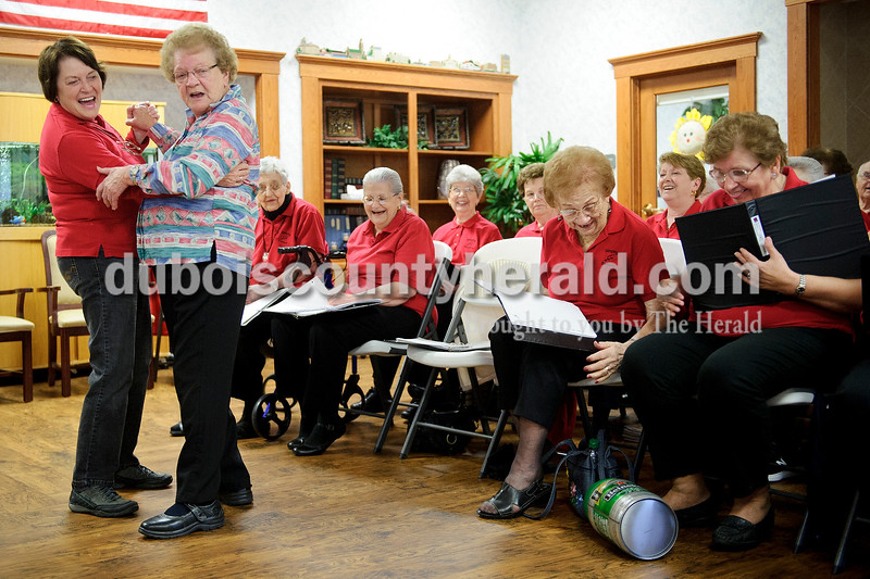 """Matthew Busch/The Herald<br /> Singing senior Viola Heitz, left, danced with resident Mary Ann Kippenbrock when fellow singer Fern Bonifer, not pictured, rolled out a Heineken beer keg as the group sang """"Beer Barrel Polka,"""" to the residents at the Northwood Retirement Community in Jasper."""