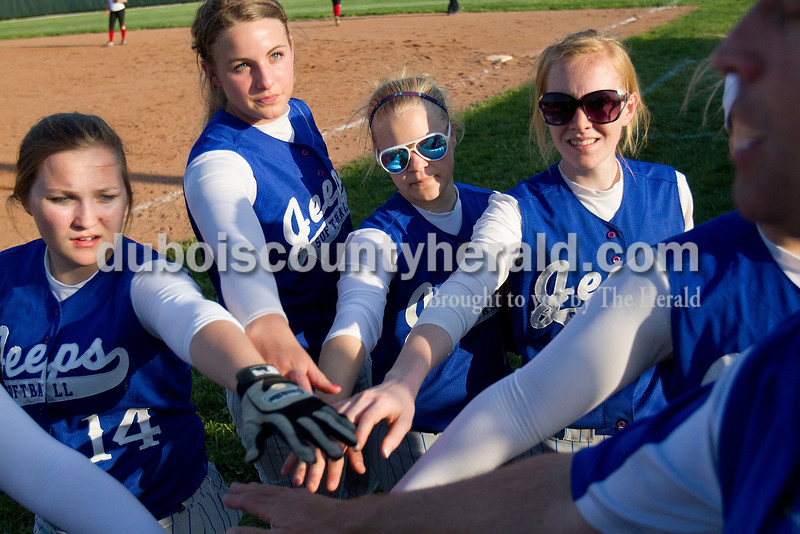 Rachel Mummey/The Herald<br /> Northeast Dubois' Taylor Knight, left, Kendra Jacob, Alexis Zehr and  Chloe Johnson huddled with teammates between innings during Monday night's game against Southridge in Huntingburg. Southridge won 6-4.