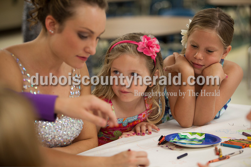 Little Miss Heimatfest contestants  Bailey Anderson of Ferdinand, 5, second from left, and Alivia Gehlhausen of St. Anthony, 8, right, watched queen contestant Shanna Hoffman of Ferdinand, 18, during an intermission of the Heimatfest Queen Pageant at the Forest Park High School on Sunday in Ferdinand. Rachel Mummey/The Herald