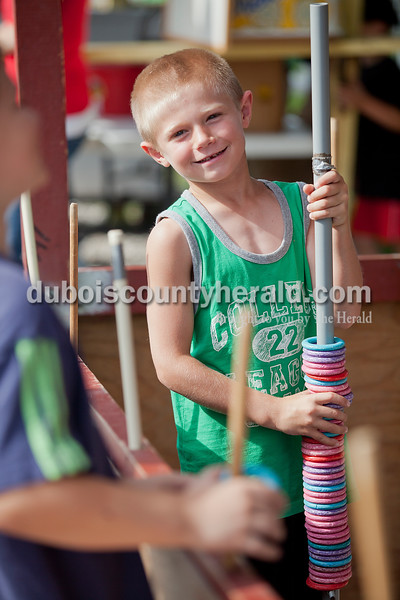 Blake Taylor of St. Henry, 7, helped out at the ring toss booth during the Heinrichsdorf Fest on the Catholic Knights of America grounds in St. Henry on Friday . Rachel Mummey/The Herald