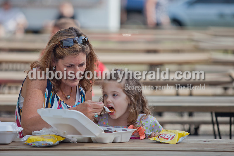 Rachel Mummey/The Herald<br /> Jan Sanders of Holland helped her granddaughter Lexi Huccaby of Bloomington, 3, try baked beans at the Heinrichdorf's Fest in St. Henry on Friday.