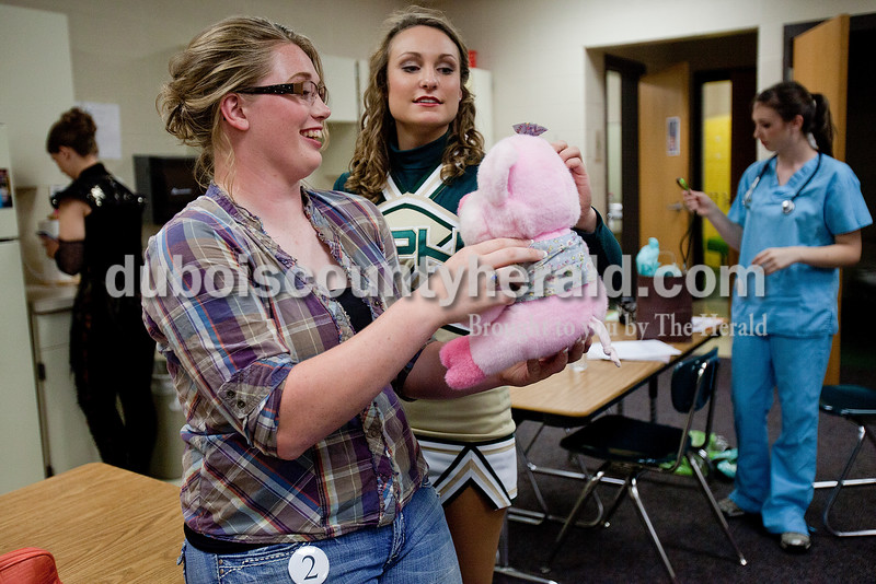 Heimatfest queen contestant Marcia Jochem of Ferdinand, 18, left, played with her stuffed pig with fellow contestant Shanna Hoffman of Ferdinand, 18, between segments of the Heimatfest Queen Pageant at the Forest Park High School on Sunday in Ferdinand. Rachel Mummey/The Herald