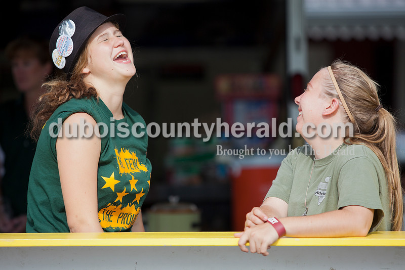 Rachel Mummey/The Herald<br /> Lauren Blume of St. Anthony, 16, and Abby Hochgesang of Birdseye, 18, shared a laugh while working the Forest Park Band Booster's booth at the Heinrichdorf's Fest in St. Henry on Friday.