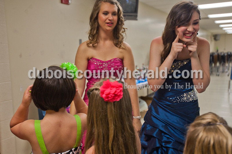 Brooke Mullen of St. Anthony, 18, right, encouraged the Little Miss contestants to smile while out on stage with fellow queen contestant Tiffany Singer of Ferdinand, 17, during the Heimatfest Queen Pageant in the auditorium at Forest Park High School on Sunday in Ferdinand. Rachel Mummey/The Herald