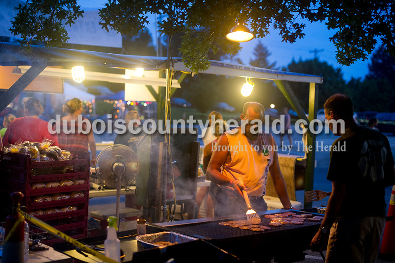 Brian Vonderheide, second from right, and Bill Mehling, right, both of Ferdinand, grilled burgers at a food stand during Heimatfest in Ferdinand on Friday.  Matthew Busch/The Herald