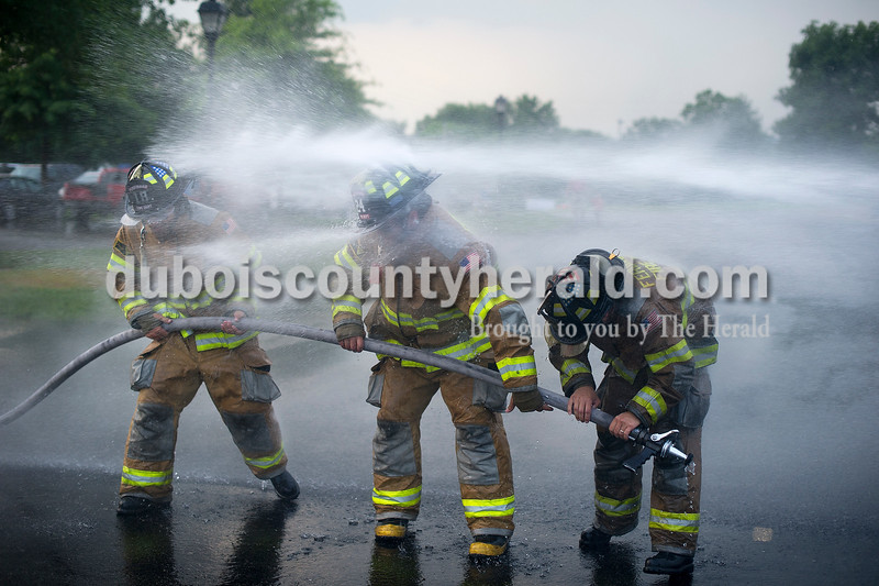 Ferdinand Volunteer Fire Department's Jarrod Oser, left, Matt Pund and Grant Kippenbrock all ducked as they were sprayed with a fire hose from members of their own department during a round of waterball at Heimatfest in Ferdinand on Friday.  Matthew Busch/The Herald