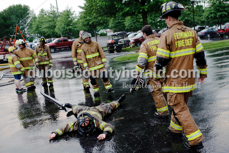 Ferdinand Volunteer Fire Department's Grant Kippenbrock feigned in exhaustion and fell over after coaching his team in a round of waterball during Heimatfest in Ferdinand on Friday.  Matthew Busch/The Herald