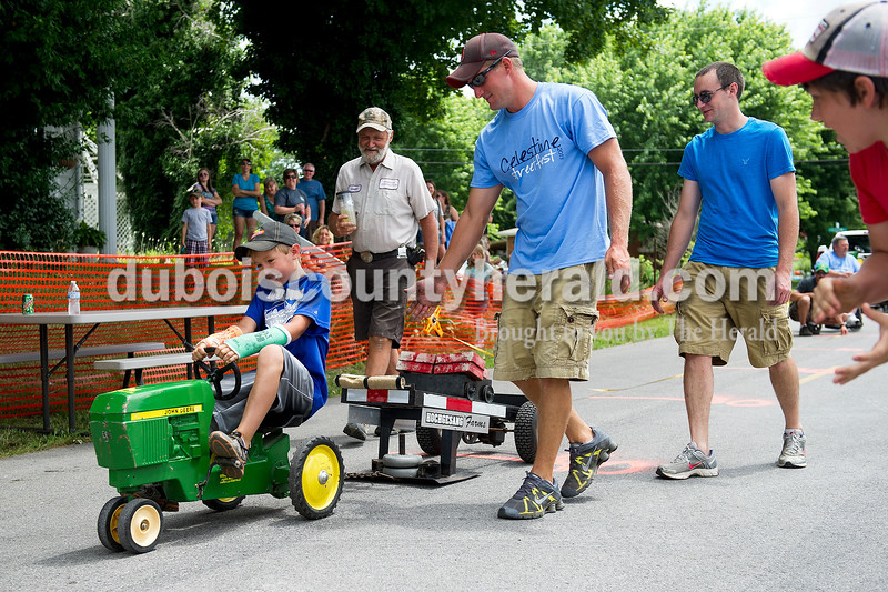 Gaige Schepers of Jasper, 8, competed in the kid tractor pull with two broken arms during the Celestine Street Fest on Saturday. Gaige won his weight group.  Matthew Busch/The Herald