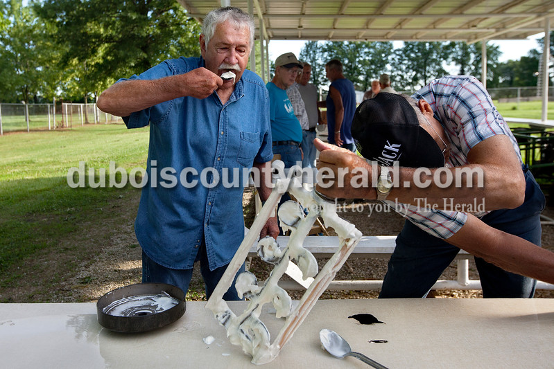 Dave Weatherwax/The Herald<br /> Roger Brittain of Petersburg, left, taste tested a batch of the homemade ice cream as Jim Houtsch of Otwell reached for the hose to spray off the dasher after pulling it from the canister containing a freshly made batch of homemade ice cream last Friday in Otwell. Brittain said he's the self-designated taste tester of the Jefferson Township Ruritan which worked that morning and into the afternoon to make about 300 gallons of homemade vanilla ice cream for the Otwell Fourth of July Celebration.