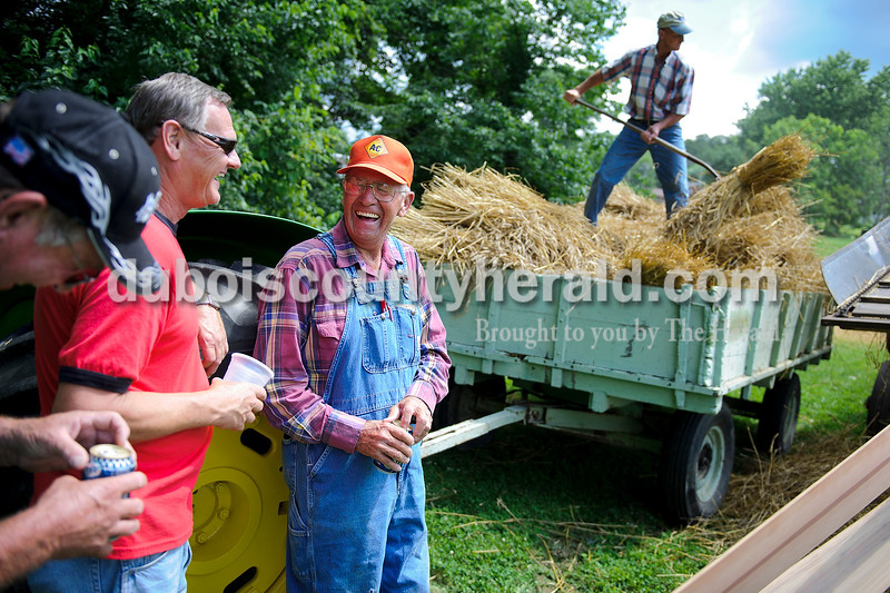 Edward Knebel of Wickliffe, left,  Allen Thewes of Celestine and John Breitweiser of Paoli enjoyed a beer after Breitweiser finished feeding wheat to the threshing machine that was on display during the Celestine Street Fest on Saturday. Breitweiser used to operate a thresher on his farm when he was younger. Hilbert Betz of Celestine, right, added more wheat to the thresher behind.  Matthew Busch/The Herald