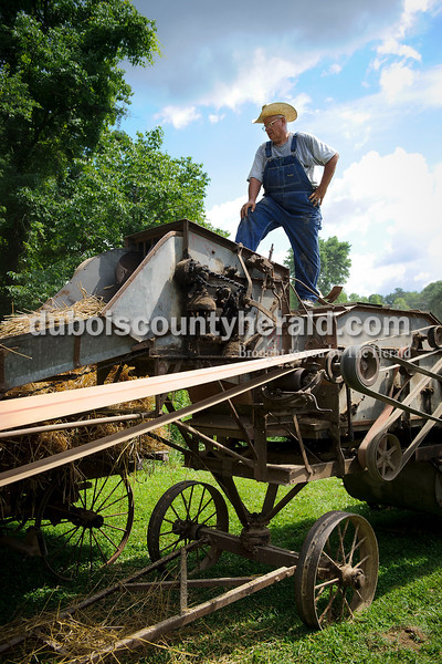 Ron Sander of Sander Farms in Celestine stood over his old threshing machine that was put to use as a demonstration during the Celestine Street Fest on Saturday.  Matthew Busch/The Herald