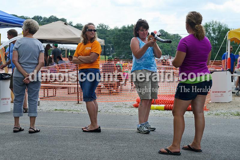 Matthew Busch/The Herald<br /> Dana Merkel of Celestine, second from right, playfully pointed her daughter's balloon gun at her friend Karen Sander of Celestine, right, during the Celestine Street Fest on Saturday.