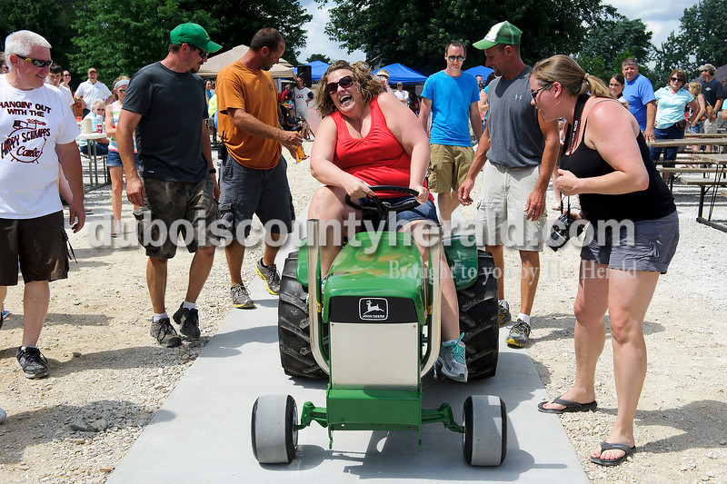 Stacy McCracken of Celestine, center, mustard all of her strength as she tried to pedal in the adult tractor pull during the Celestine Street Fest on Saturday. McCracken's sister Kim Bayer of Jasper, right, encouraged on..  Matthew Busch/The Herald