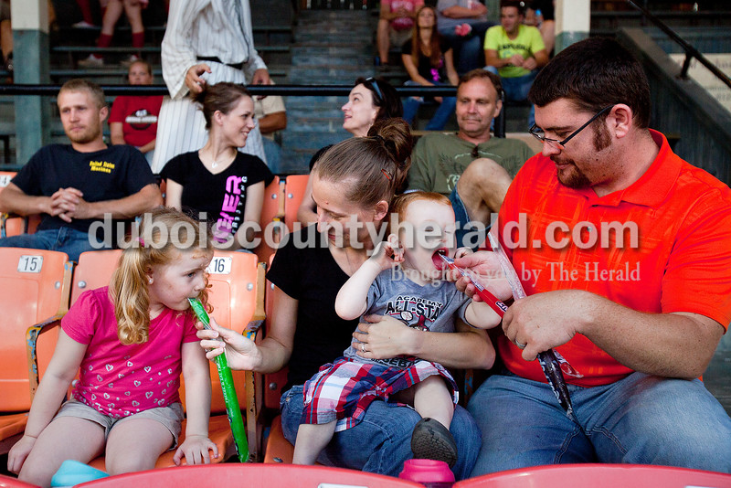 Leah Adams of Winslow, second from left, and her husband, Justin, right, helped their children, Jocelyn, 3, left, and Josiah, 1, with their icy pops during Tuesday night's Dubois County Bombers game against the Hoptown Hoppers at League Stadium in Huntingburg. The family attended the game as part of the corporate sponsorship by Meyer Distributing, which is where Leah works.  Rachel Mummey/The Herald