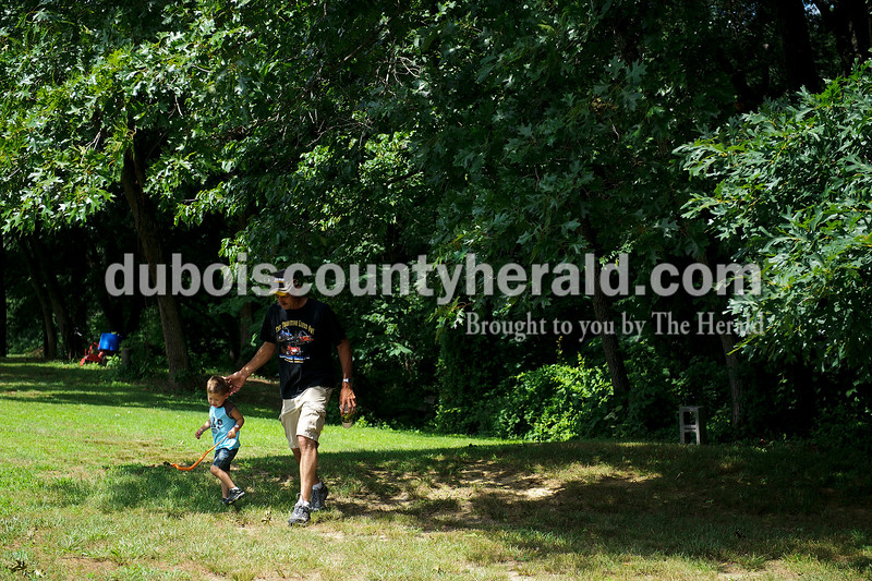 Daryl Betz of Celestine walked with his son Halton Betz, 2, after looking around in the woods during the Celestine Street Fest on Saturday.  Matthew Busch/The Herald