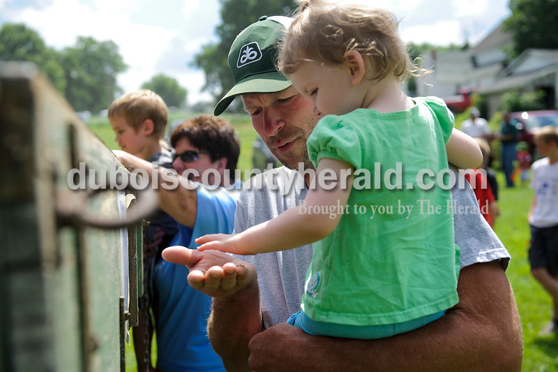 Chris Hasenour of Celestine showed his daughter Allison, 2, the grain that was produced using a thresher from Sander Farms during the Celestine Street Fest on Saturday.  Matthew Busch/The Herald