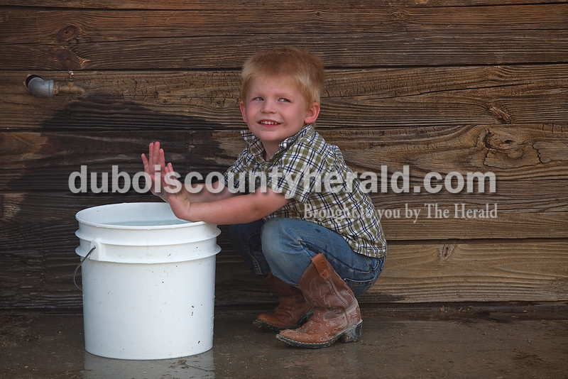 Austin Oeding of Ferdinand, 3, played with a bucket of water between the swine barn and the cattle barn at the Dubois County 4-H Fairgrounds on Sunday. Rachel Mummey/The Herald